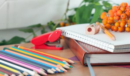 teaching material: Colored pencils and a notebook on the table. Photos school supplies