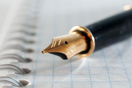 Gold fountain pen close-up on notebook sheet. Photo closeup Pen