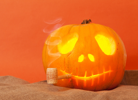 smoking pipe: Beautiful Pumpkin on Halloween with a pipe on an orange background