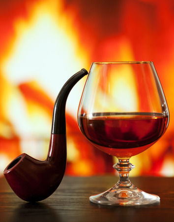 smoking pipe: Brandy glass and smoking pipe on the table near the burning fireplace Stock Photo