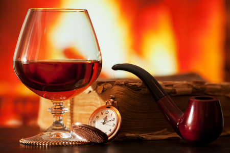smoking pipe: Brandy glass, old book, smoking pipe, and pocket watch on the table near the burning fireplace