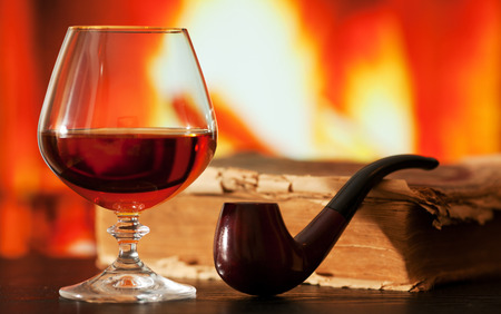 smoking pipe: Brandy glass, old book and smoking pipe on the table near the burning fireplace Stock Photo