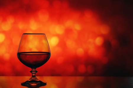 Brandy glass on the bright blurred background with bokeh