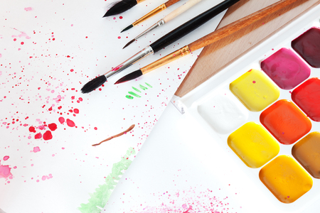 Colored paints, brushes and paper on the table Stock Photo