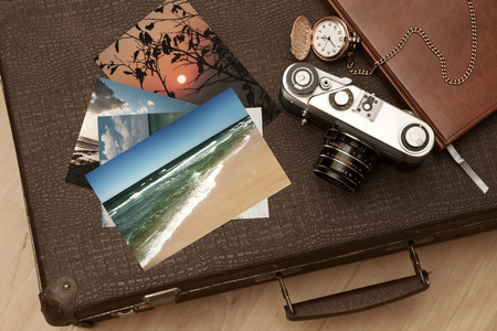 Photos and an old retro camera on a suitcase