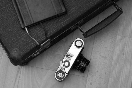 Old retro camera and travel bag on the floor