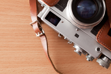 Old retro camera lies on a table Stock Photo