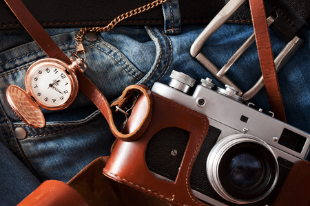 Old retro camera and pocket watch lies on a jeans Stock Photo