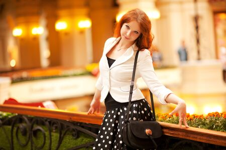 Beautiful red-haired woman walking in the mall Stock Photo