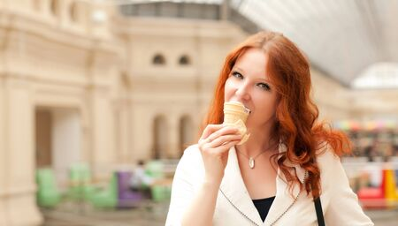 Beautiful red-haired woman is eating ice cream and walking in the mall