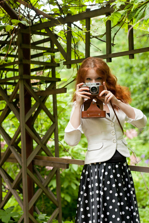 Woman with an old vintage camera in the park