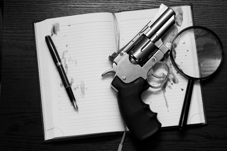 noire: Revolver, open notebook and a magnifying glass on the table