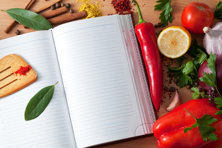 the recipe to write down: Ingredients for a dish and notebook on a table Stock Photo