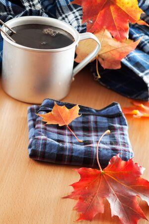 Tea mug, handkerchief and autumn leaves on the table