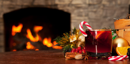 Mulled wine and candy on the table near the fireplace Stock Photo