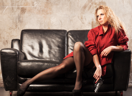 A woman with beautiful legs and a revolver in her hands is lying on the couch 스톡 콘텐츠