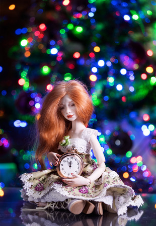 Beautiful red-haired doll is holding a clock in her hands