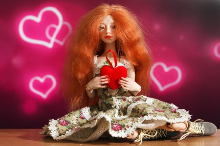 Red-haired doll and heart on a beautiful background Stock Photo