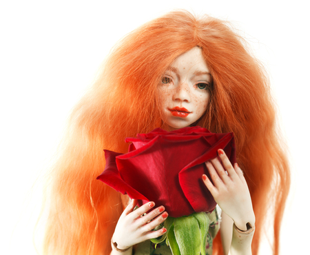 Beautiful red-haired doll and red rose close-up on white Stock Photo