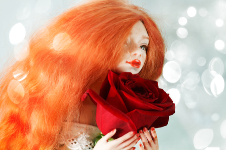 Beautiful red-haired doll and red rose close-up
