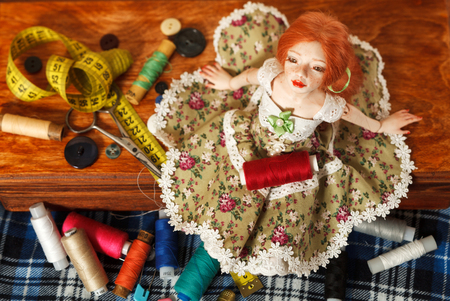 Photo of a beautiful doll and sewing accessories on a table
