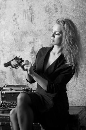Beautiful woman with a revolver in her hands