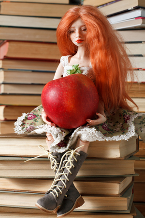 Beautiful doll with an apple near the books