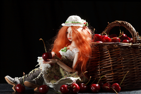 Beautiful doll and cherry in a basket on a black background