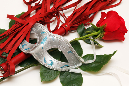 Red whip, rose and mask on a white