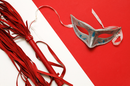 Whip and mask on a red and white background