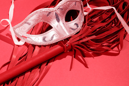 Whip and mask on a red  background