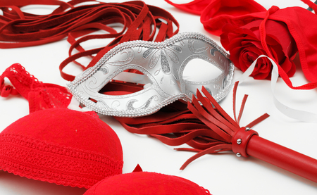Red whip, mask and lingerie on a white background Stock Photo