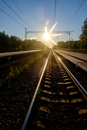 The railroad going into the distance and the rising sun Stock Photo
