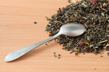 Background with green tea. Dried green tea leaves on the table. Spilled tea leaves and a teaspoon.