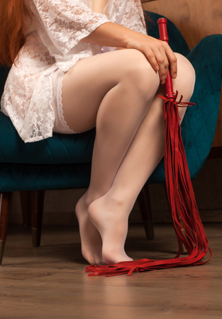 Beautiful female legs in white stockings and a red whip