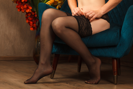 Woman dressing stockings sitting in a chair. Beautiful female legs in black stockings Stock Photo