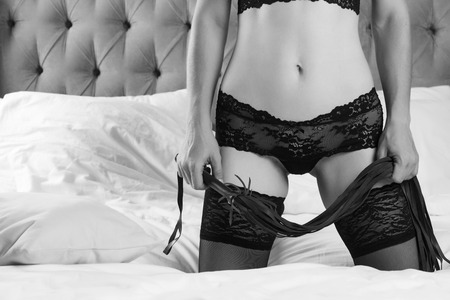 Slim woman in black lingerie and whip Stock Photo