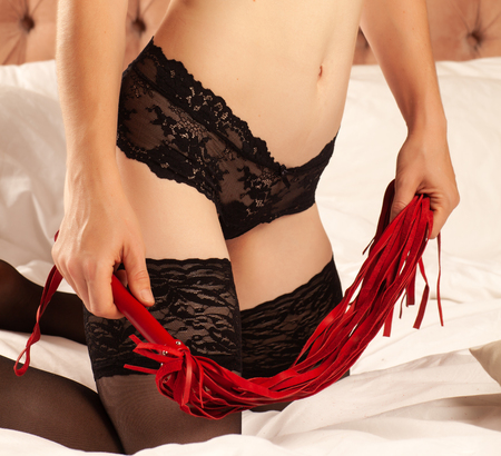 Slim woman in black lingerie and red whip