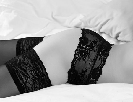 A woman in black panties and stockings is lying on the bed Stock Photo