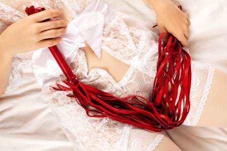 Woman in lingerie with whip lying on the bed