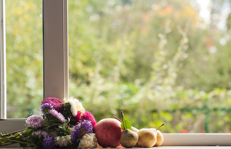 Flowers and fruits on the window with a blurred background