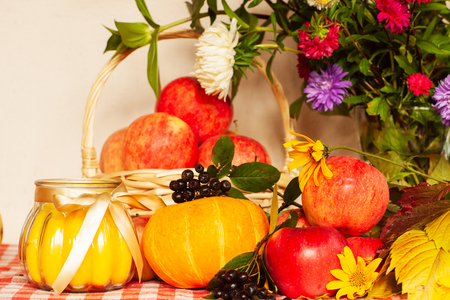 Autumn composition of pumpkin, apples and flowers on the table Stock Photo