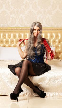Langhaarige Frau im Korsett mit roter Peitsche sitzt auf dem Bett