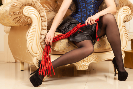 Beautiful female legs in black shoes with high heels and red whip