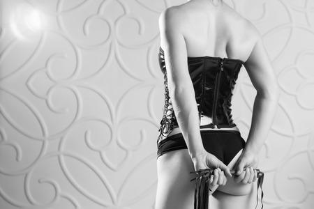 Schöne schlanke Frau in einem schwarzen Korsett hält eine Peitsche Standard-Bild