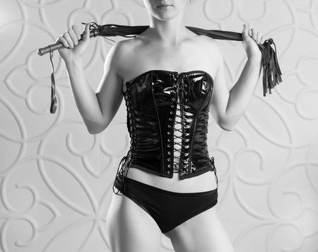Beautiful slim woman in a black corset holds a red whip Stock Photo