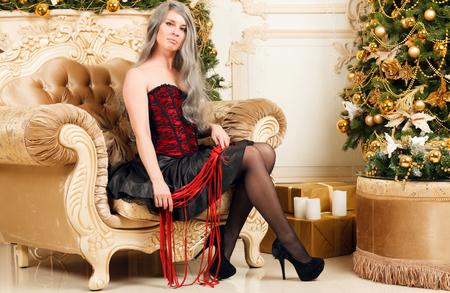 Frau mit Peitsche sitzt neben dem Weihnachtsbaum