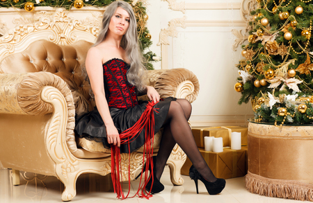 Woman with a whip sitting near the Christmas tree Banco de Imagens