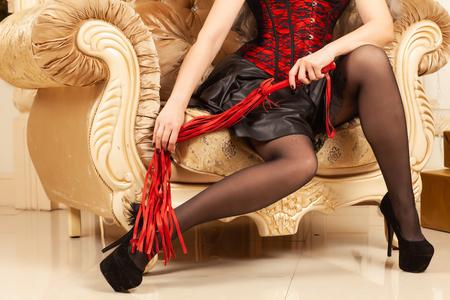 Schöne weibliche Beine in schwarzen Schuhen mit hohen Absätzen und roter Peitsche