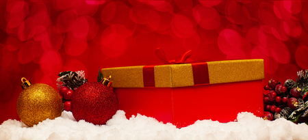 Gift and Christmas balls on snow on a red background Stock Photo